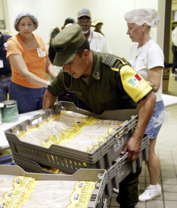 SAN ANTONIO - SEPTEMBER 9: A Mexican soldier moves loaves of bread in preparation for the noon meal for the evacuees located in San Antonio. The Mexican Army will be in San Antonio for 20 days to provide humanitarian relief. This is the first time the Mexican Army has been in San Antonio since 1846. (Photo by Joe Mitchell/Getty Images)