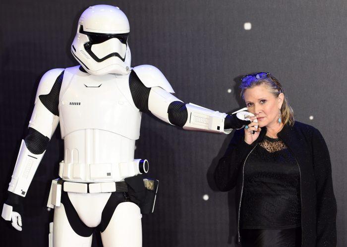 """FA0031- LONDRES (REINO UNIDO), 16/12/2015.- La actriz estadounidense del reparto Carrie Fisher posa junto a uno de los personajes Stormtrooper en la alfombra roja hoy, miércoles 16 de diciembre de 2015, en el prestreno de la película """"Star Wars: El despertar de la Fuerza"""", en Leicester square en Londres, Reino Unido. Se estrena el séptimo episodio de la saga con la que George Lucas revolucionó el negocio del cine hace casi cuatro décadas. EFE/FACUNDO ARRIZABALAGA"""